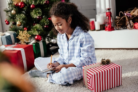 Adorable African American child in pajamas writing something to copybook at home, Christmas concept