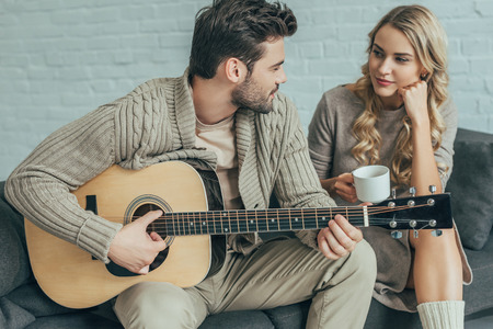 Attractive young man playing guitar for girlfriend at home while she sitting on couch with coffee