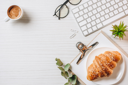 Elevated view of workplace with croissant, coffee cup and computer keyboard in office