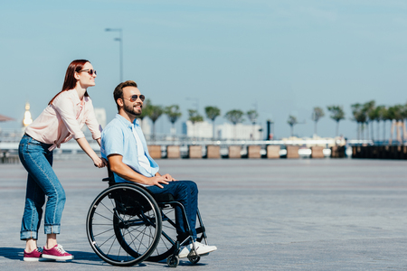 Side view of smiling attractive girlfriend pushing handsome boyfriend in wheelchair on street