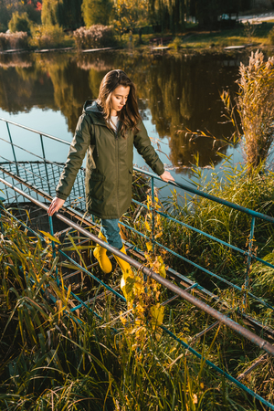 High angle view of young woman in jacket and yellow rubber boots posing near pond in park