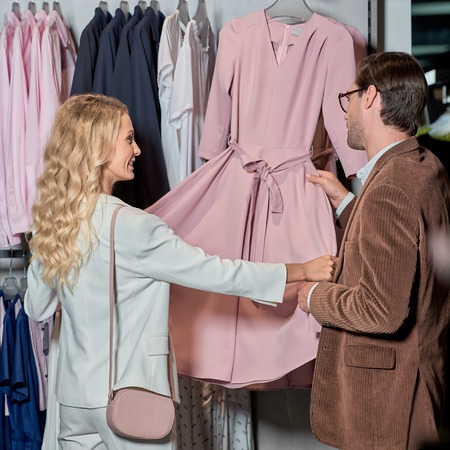 Couple looking at fashionable pink dress in boutique Foto de archivo - 111391409