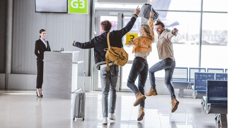 Back view of excited young friends running to check-in desk in airport