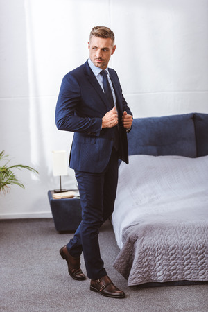 Full length view of handsome adult man wearing suit jacket and looking away in bedroom Foto de archivo