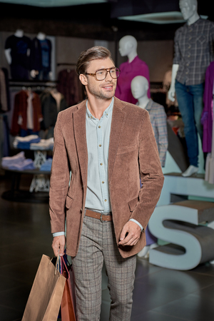 Handsome smiling man in eyeglasses holding shopping bags and looking away in fashion store Foto de archivo - 111391424