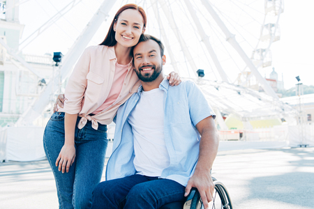 Smiling handsome boyfriend in wheelchair and girlfriend hugging and looking at camera on street near observation wheel