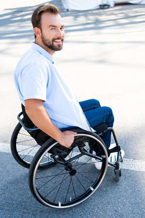 Handsome smiling man using wheelchair on street and looking at camera Stock Photo