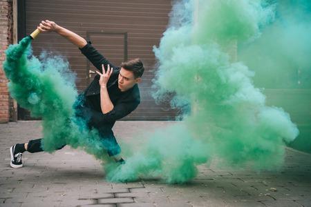 Beau jeune danseur dans la fumée verte dans la rue