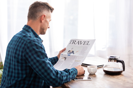 Rear view of man sitting at table and reading travel newspaper in kitchen at home Standard-Bild - 111391456