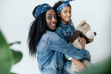 Portrait of cheerful African American woman hugging little daughter with teddy bear at home