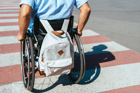 Cropped image of disabled man in wheelchair with bag riding on crosswalk