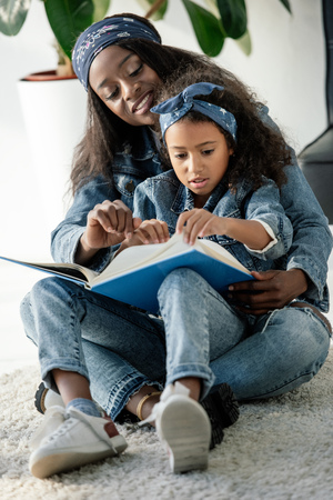 African American mother and daughter looking at family photo album at home 写真素材