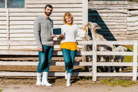Man showing digital tablet with girlfriend while she feeding goat at farm