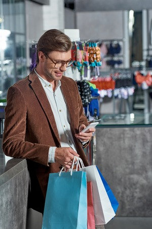 Handsome smiling man in eyeglasses holding paper bags and using smartphone in shop Foto de archivo - 111391623