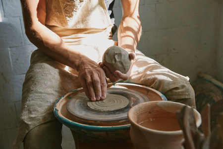 Partial view of professional potter working with clay at workshop Stok Fotoğraf