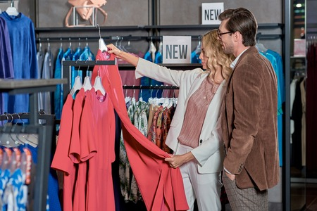 Stylish couple choosing fashionable clothes in store
