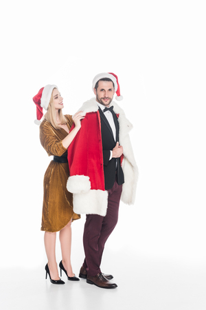 Young woman putting Santa Claus costume on boyfriend isolated on white background Standard-Bild