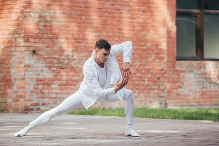 Handsome young male dancer in white clothes practicing on street