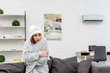 Freezed young woman in warm clothes sitting on couch at home with air condition hanging on background Stock fotó