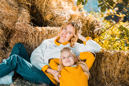 Attractive woman posing with little daughter on hay stacks at farm