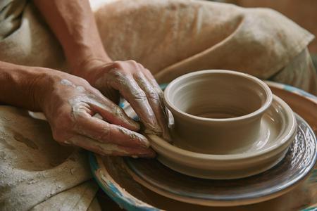 Vue rapprochée d'un potier professionnel travaillant sur un tour de potier à l'atelier