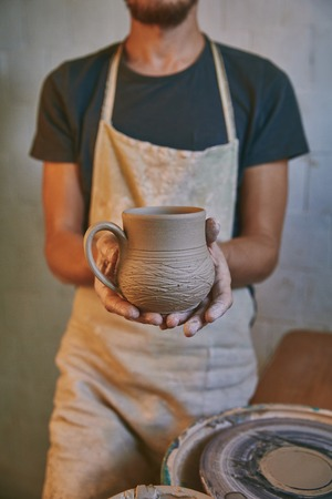 Cropped image of potter in apron holding clay pot at workshop