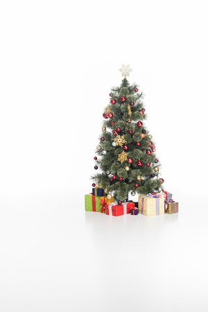 Close up view of festive Christmas tree and wrapped gifts isolated on white background