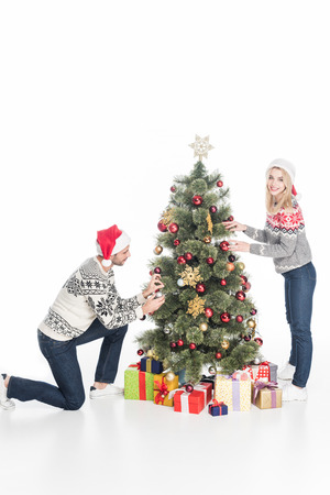 Young couple in Santa Claus hats decorating Christmas tree together isolated on white background