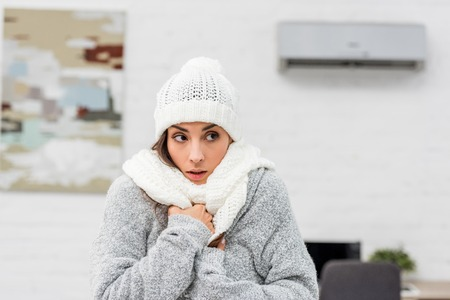 Close-up portrait of freezing young woman in warm clothes with air conditioner on background Archivio Fotografico - 111392283