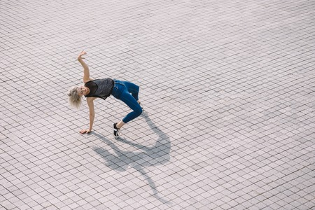 High angle view of attractive girl dancing on city street