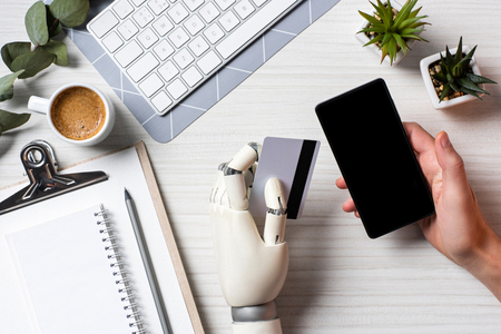 Cropped image of businessman with prosthesis arm holding credit card and using smartphone with blank screen at table in office