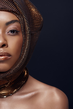 Partial view of attractive African American model with head wrap isolated on black background