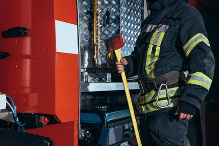 Partial view of firefighter in fireproof uniform holding axe at fire department