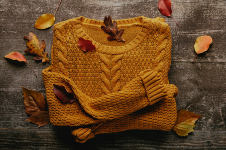 Flat lay with fallen leaves and orange sweater on wooden tabletop