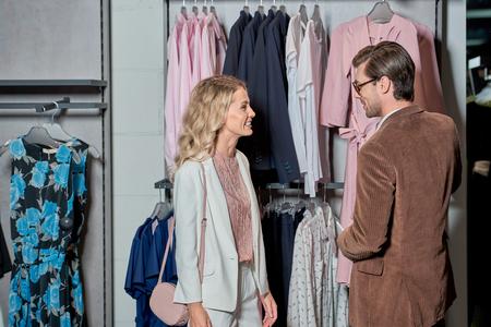 Smiling young couple choosing fashionable clothes in shop Foto de archivo - 111392398
