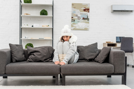Freezed young woman in warm clothes sitting on sofa at living room Reklamní fotografie