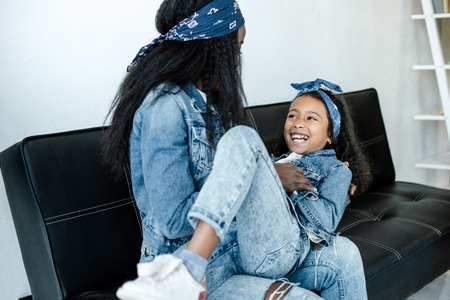 African American woman and cheerful daughter having fun on sofa at home 스톡 콘텐츠