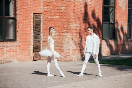 Young ballet dancers in white clothes dancing on urban street Foto de archivo - 111396600