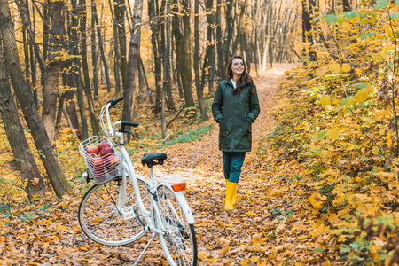 Girl in yellow rubber boots walking near bicycle in autumnal forest