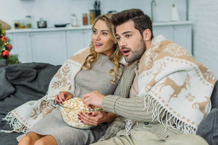 Excited young couple with popcorn watching movie at home