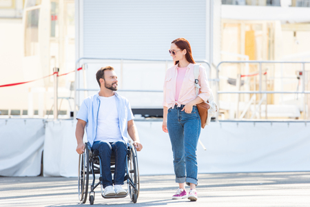 Handsome boyfriend in wheelchair and girlfriend walking and  looking at each other on street Stock Photo