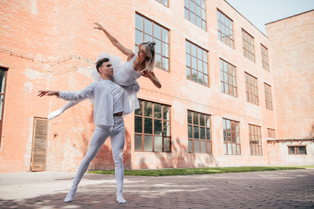 Young ballet dancers in white clothes dancing on urban city street