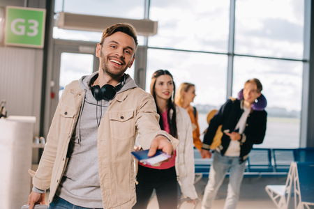 Happy young man holding passport with boarding pass and smiling at camera in airport Stock Photo