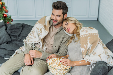 High angle view of beautiful young couple with popcorn watching movie at home Stock Photo