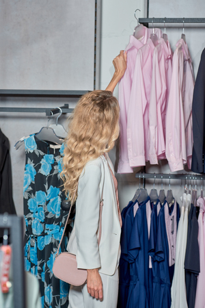 Beautiful young woman looking at stylish shirts in fashion store Foto de archivo - 111396890