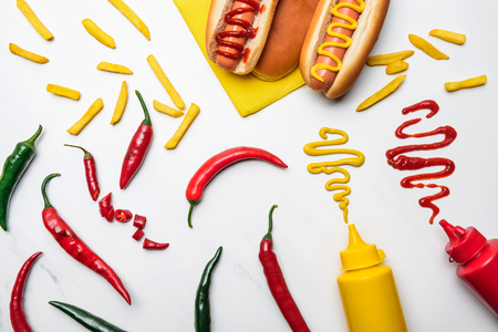 Top view of delicious hot dogs and peppers with mustard and ketchup on white marble surface