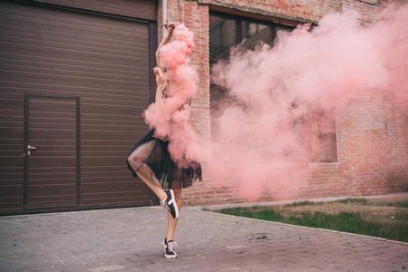 Young female contemporary dancer in pink smoke on street Stockfoto