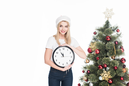 Portrait of young woman in Santa Claus hat holding clock near Christmas tree isolated on white background