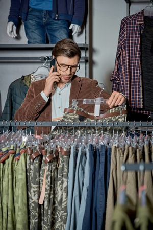 Man in eyeglasses talking by smartphone and choosing fashionable clothes in shop