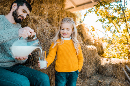 Adult female farmer pouring milk to little daughter near hay stacks at ranch